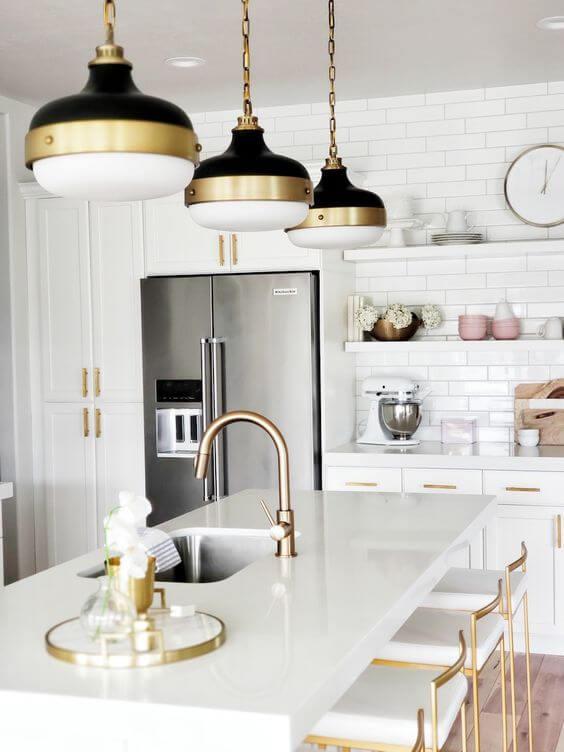 Bancada de cozinha de granito branco com luminárias douradas