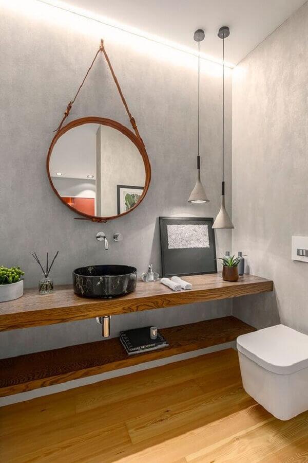 banheiro cimento queimado decorado com bancada de madeira e espelho redondo  Foto Casa de Valentina