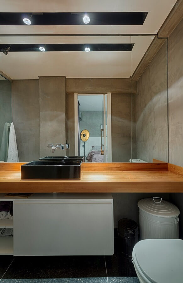 banheiro com parede de cimento queimado decorado com bancada de madeira com cuba preta Foto Piacesi Arquitetura