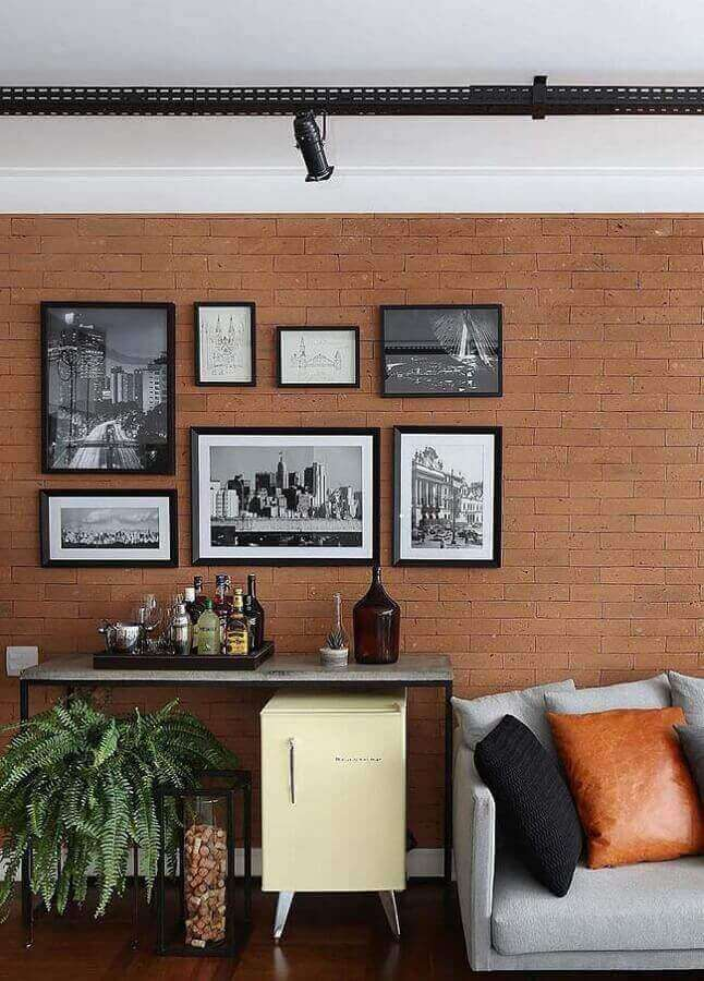 Parede com quadros para sala decorada com sofá cinza e parede de tijolinho