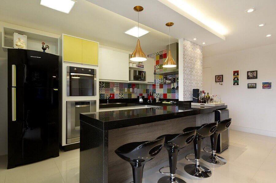 cozinha americana com balcão preto decorada com revestimento colorido Foto Juliana Conforto Interiores