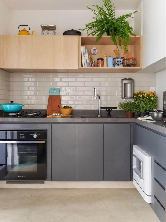 cozinha com balcão de canto decorada com armário aéreo de madeira e metro white branco  Foto SP Estúdio Arquitetura