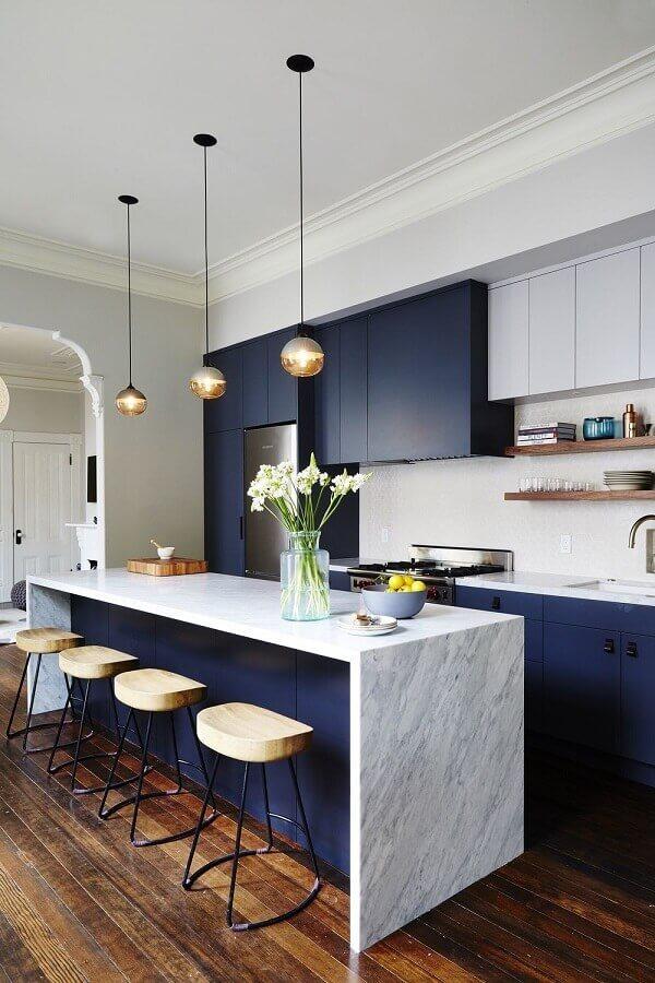 cozinha com balcão de mármore no meio decorada com armários azuis  Foto McGee & Co.