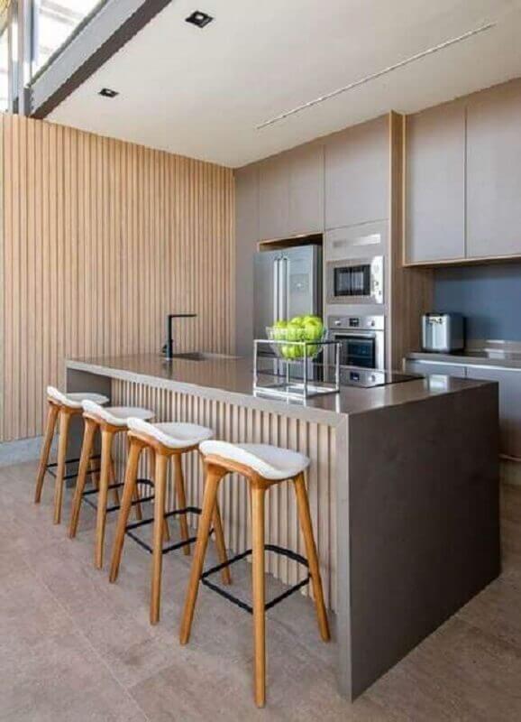 cozinha com balcão no meio decorada com revestimento de madeira  Foto Casa de Valentina