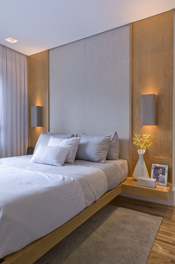 decoração com luminária de parede para quarto com parede amadeirada e cabeceira cinza Foto Débora Aguiar