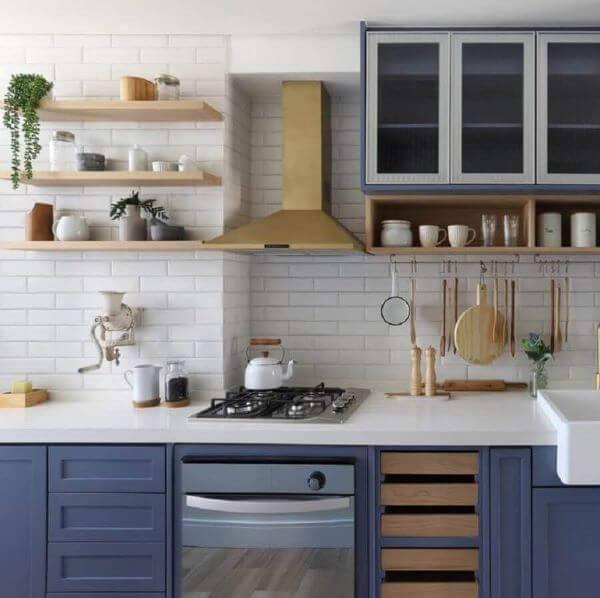 Cozinha com armários azuis e prateleira de madeira