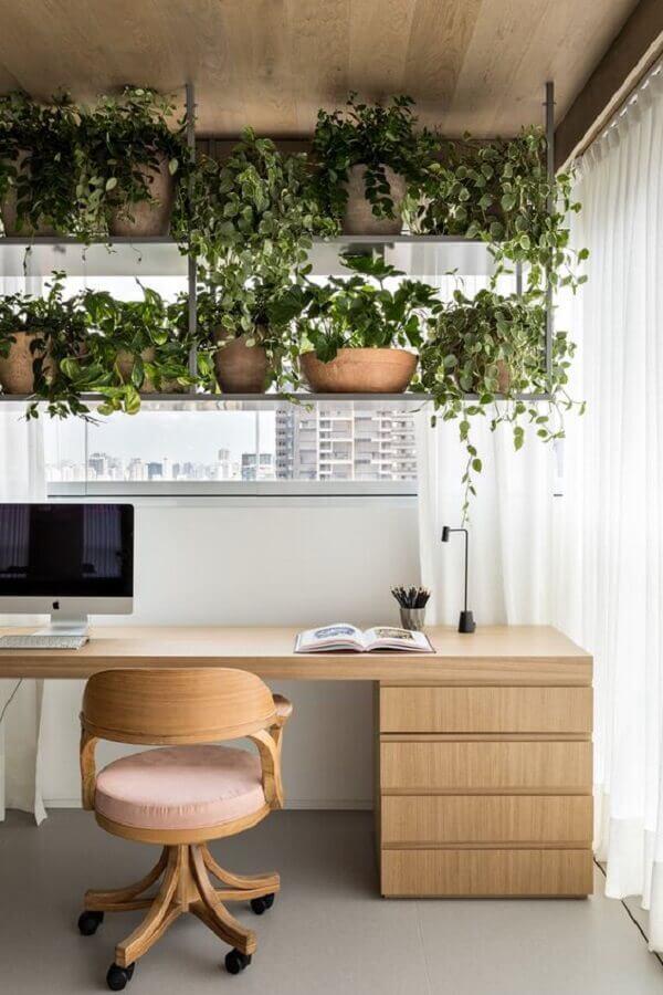 decoração com vasos de plantas e mesa de estudo com cadeira de madeira giratória Foto Archdaily
