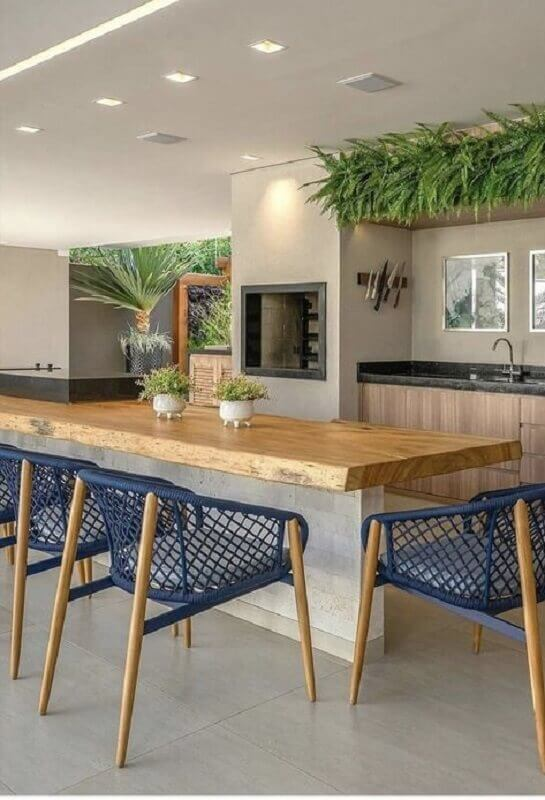 decoração de área gourmet moderna com churrasqueira e bancada de madeira rústica Foto Jeito de Casa