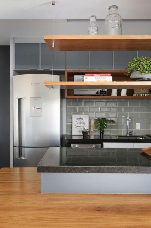 decoração de cozinha planejada com prateleiras de madeira e revestimento metro cinza Foto Jeito de Casa