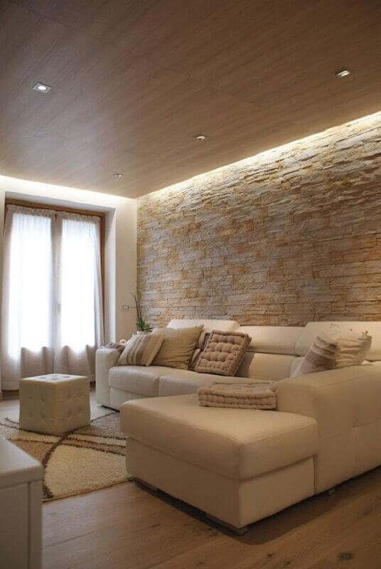 decoração em cores neutras com almofadas para sala com parede rústica  Foto Homify