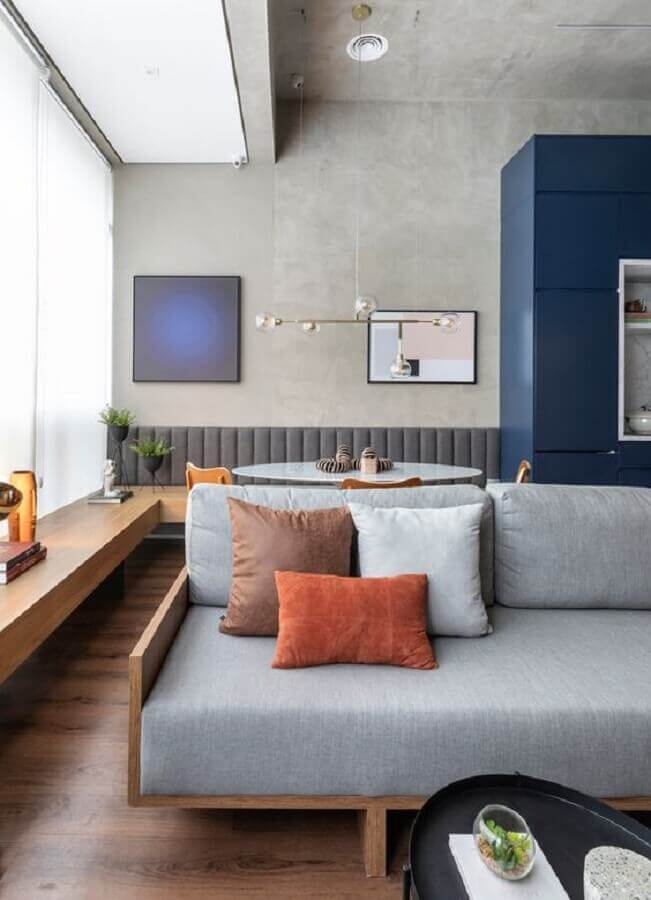 decoração estilo industrial com  almofadas para sala com sofá de madeira e parede de cimento queimado Foto Archdaily