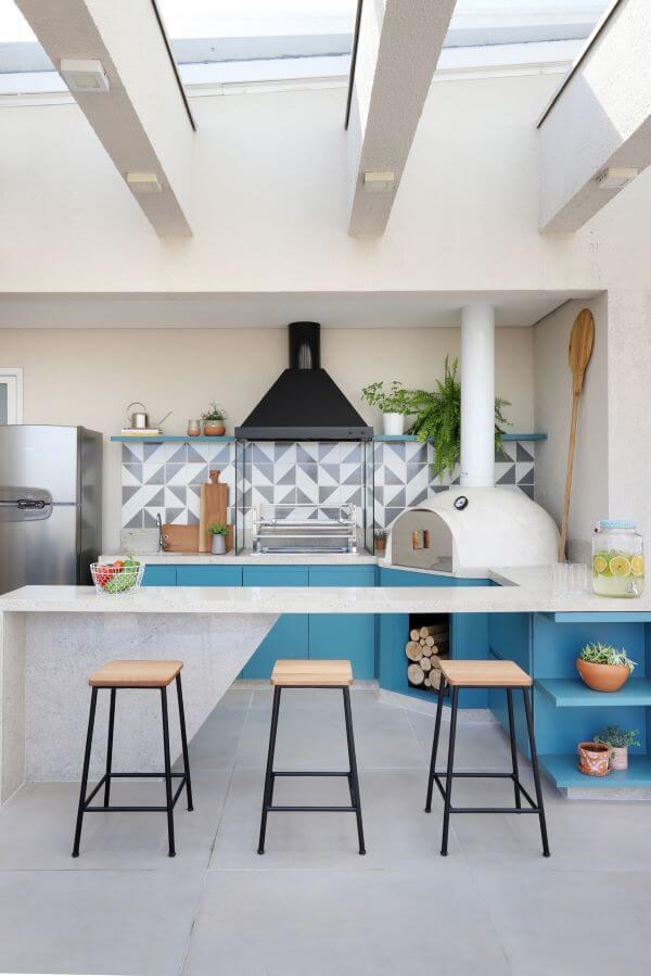 Área gourmet com bancada de granito branca e armários azuis