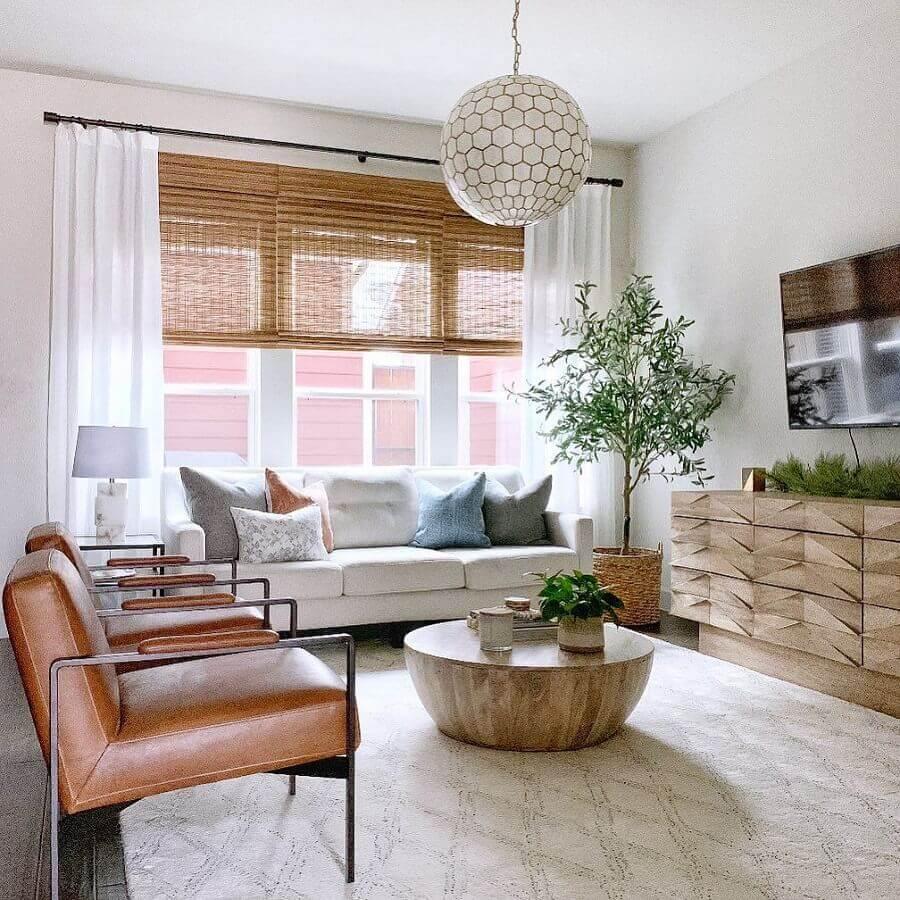 mesa de centro redonda de madeira para decoração de sala com poltronas de couro modernas Foto Serena & Lily