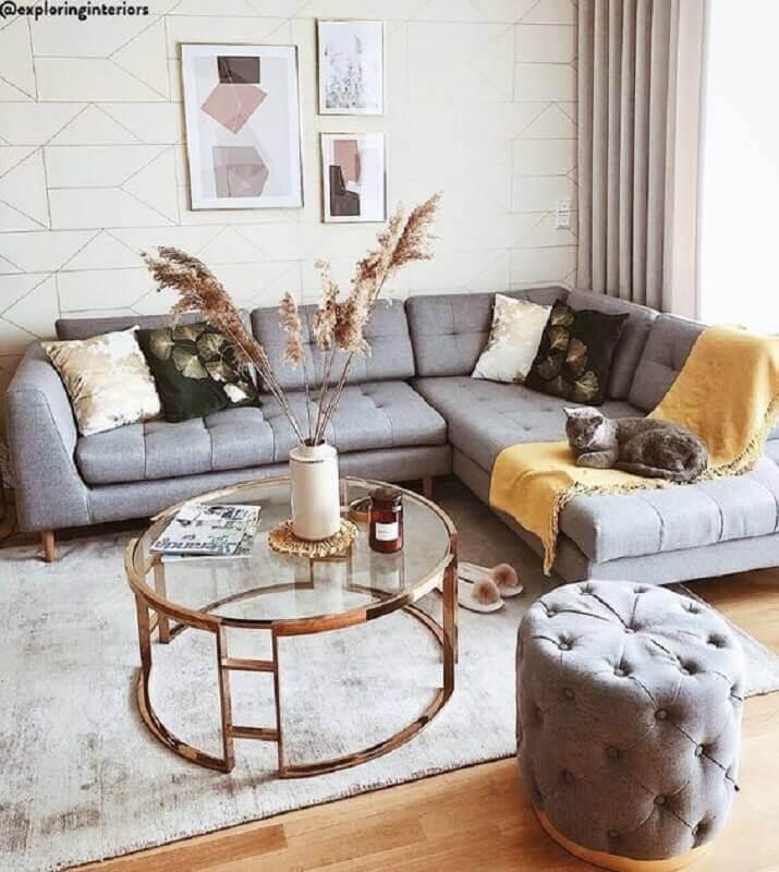mesa de centro redonda de vidro para sala decorada com sofá de canto cinza e puff capitonê Foto Jeito de Casa