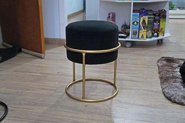 Modelo de puff preto redondo com estrutura dourada