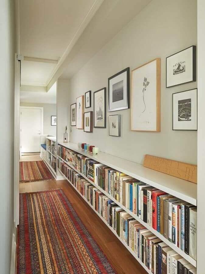 parede com quadros para corredor decorado com estante de livros Foto Histórias de Casa