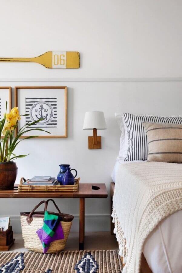 quarto branco decorado com luminária de parede e banco de madeira Foto Histórias de Casa