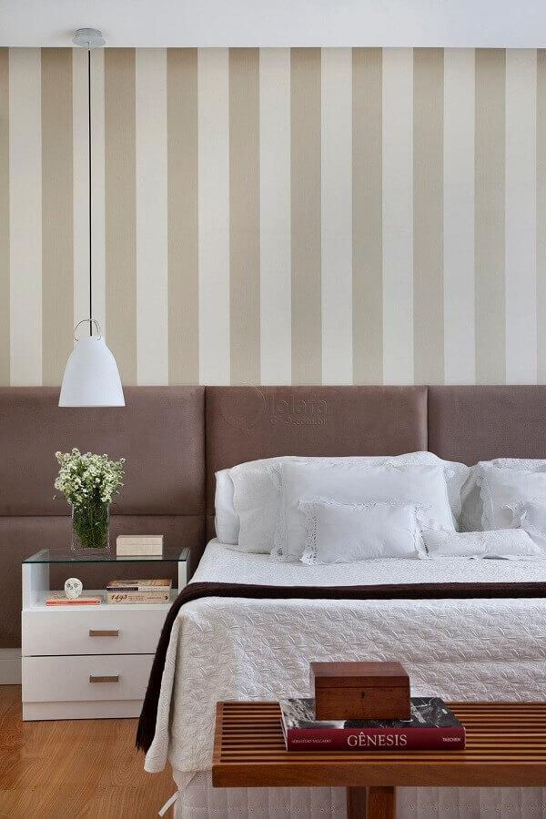 quarto de casal bege decorado com papel de parede listrado e cabeceira estofada Foto Lolafá