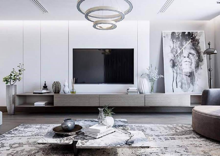 sala branca moderna decorada com quadro grande apoiado no rack Foto Pinterest