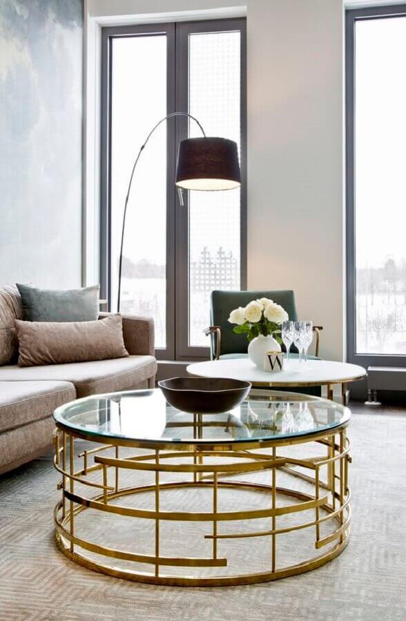 sala de estar decorada com mesa de centro redonda de vidro com estrutura dourada Foto Homedit