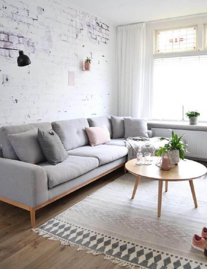 sala minimalista decorada com sofá cinza claro e mesa de centro redonda de madeira Foto Casa de Valentina