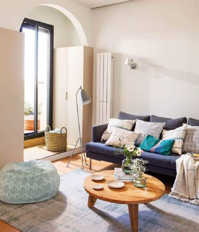 sala simples decorada com mesa de centro redonda de madeira e sofá azul marinho Foto El Mueble