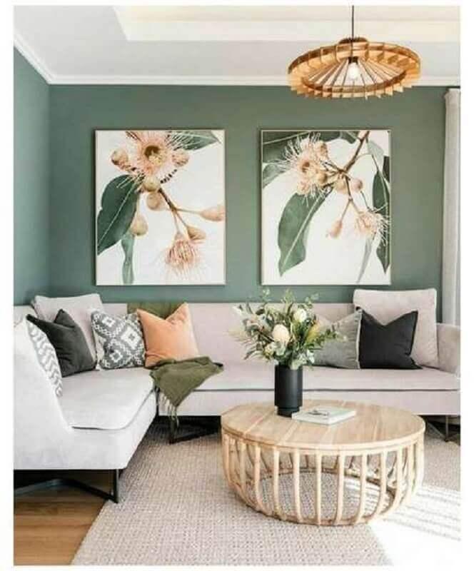 sala verde decorada com sofá de canto e mesa de centro redonda de madeira Foto Jeito de Casa