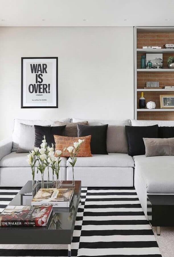 sofá com chaise com almofadas para sala decorada com tapete listrado  Foto Histórias de Casa
