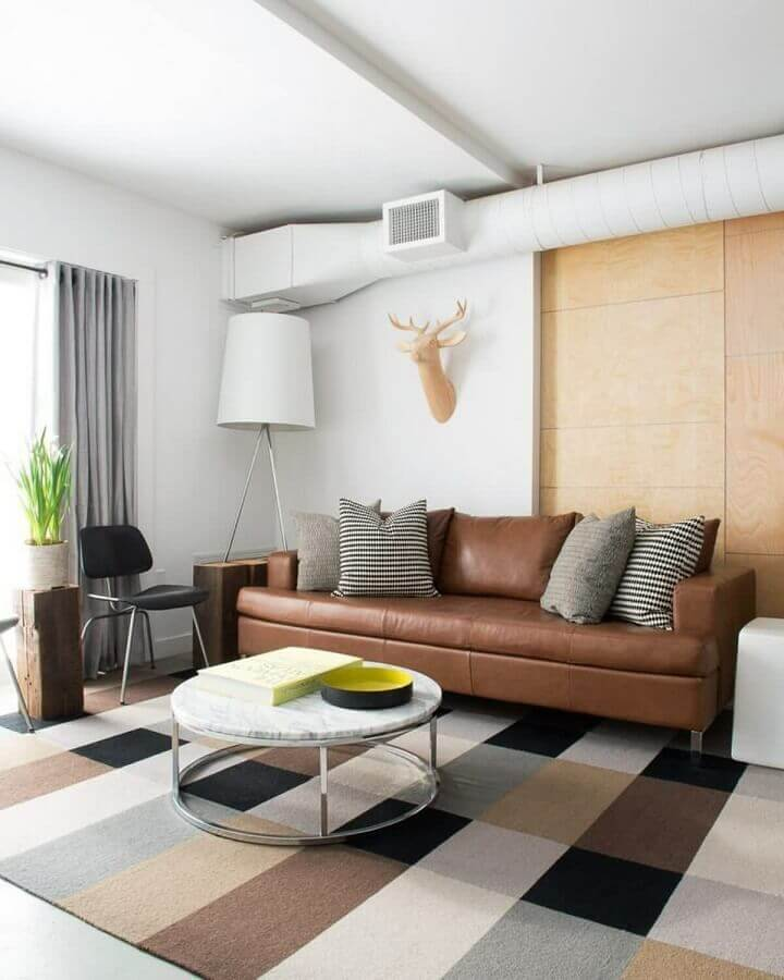 sofá de couro com almofadas para sala de estar decorada com tapete quadriculado e mesa de centro redonda Foto Houzz
