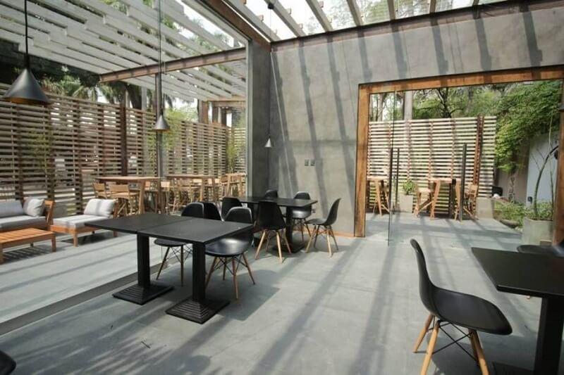 Área externa com cobertura de vidro e piso fosco de cimento queimado. Projeto de Casa Cor Paraguai