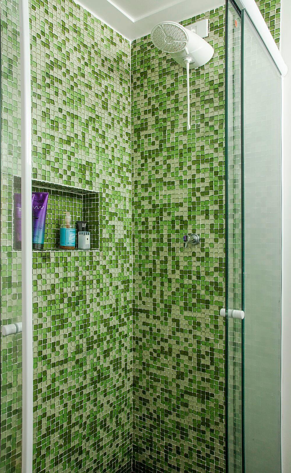 Na área do banho as pastilhas de vidro verde trazem um toque de cor para o cômodo. Foto: Luis Gomes