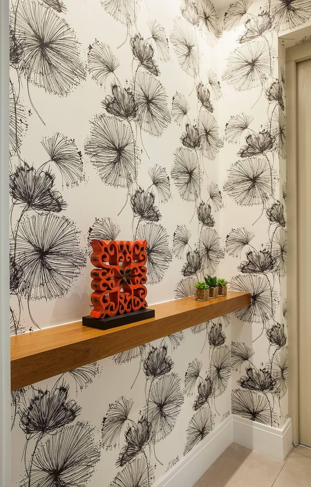 A decoração tanto da entrada do elevador como do lavabo seguem o mesmo papel de parede floral. Foto: Eduardo Pozella