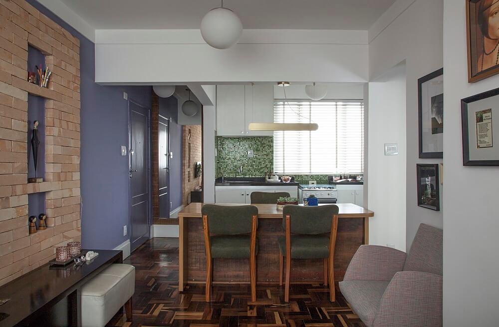 As cadeiras de lona verde da mesa de jantar se conectam com as pastilhas de vidro da cozinha. Foto: Luis Gomes