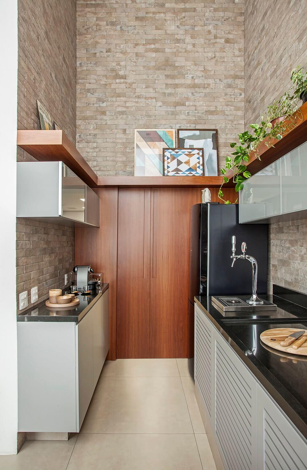 Nas paredes os bricks rústicos agregam valor ao décor e as prateleiras de madeira servem de apoio para quadros e vasos. Foto: Eduardo Pozella