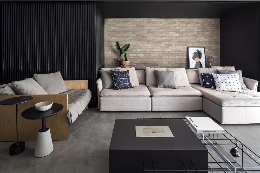 O pórtico em Fresno Negro emoldura o revestimento de tijolo em concreto atrás do sofá. Foto: Divulgação UNIC Arquitetura