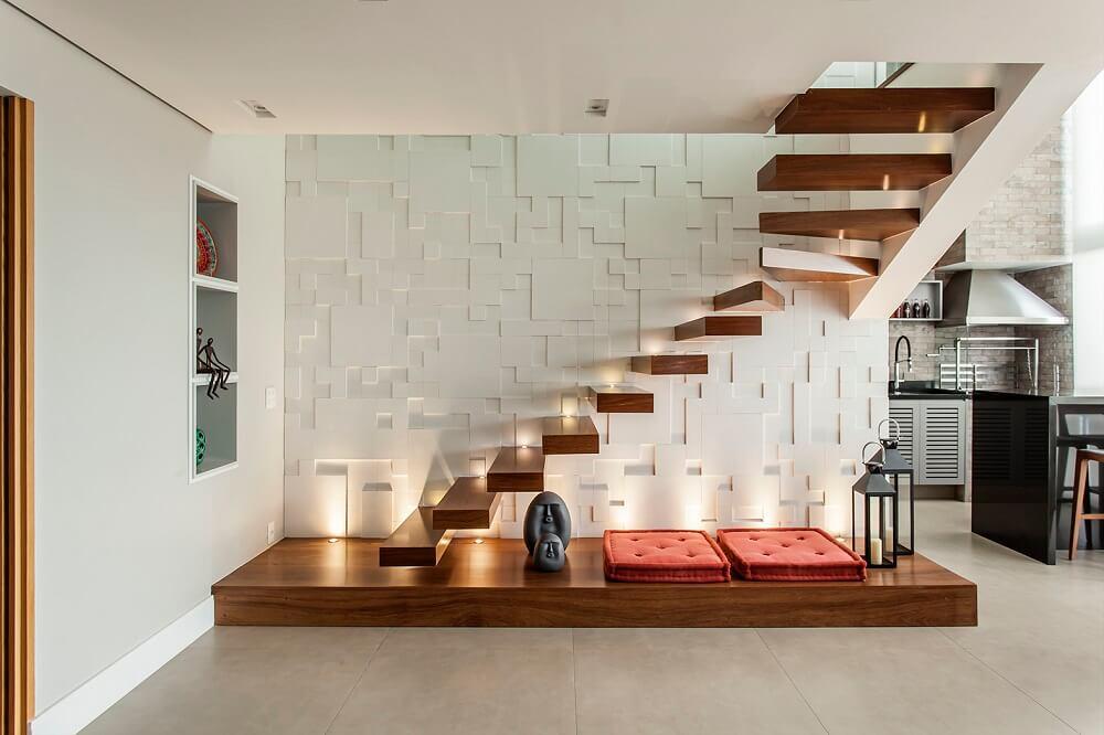 Revestimento 3D e luzes pontuais nos degraus da escada flutuante de madeira trazem charme para a decoração. Foto: Eduardo Pozella