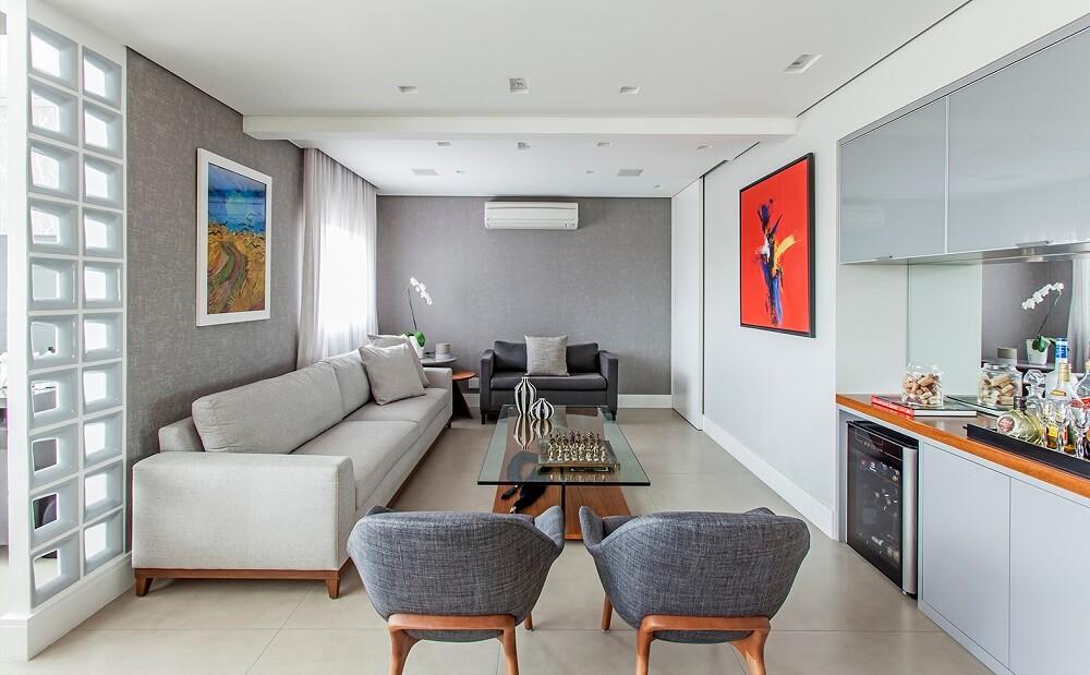 Para a sala de estar sofá branco, poltronas em tom cinza e quadros coloridos. Foto: Eduardo Pozella
