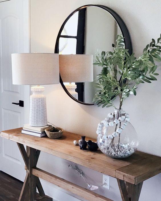 Aparador rustico decorado com abajur branco e espelho redondo