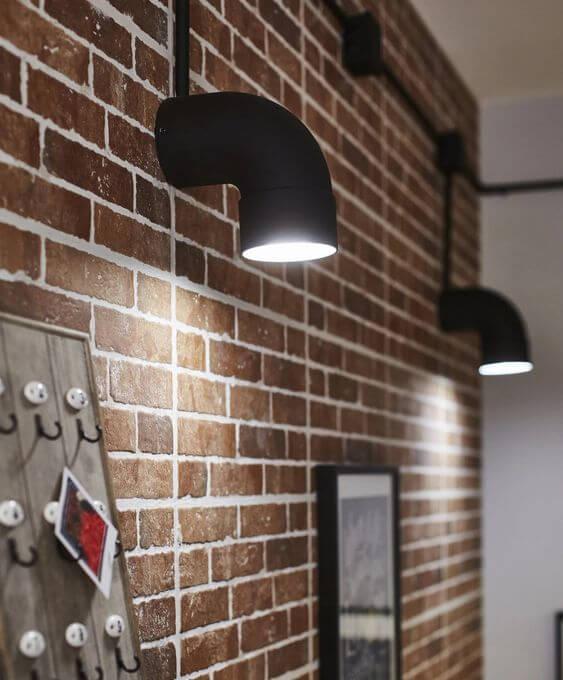 Arandela industrial de pvc na parede de tijolinho