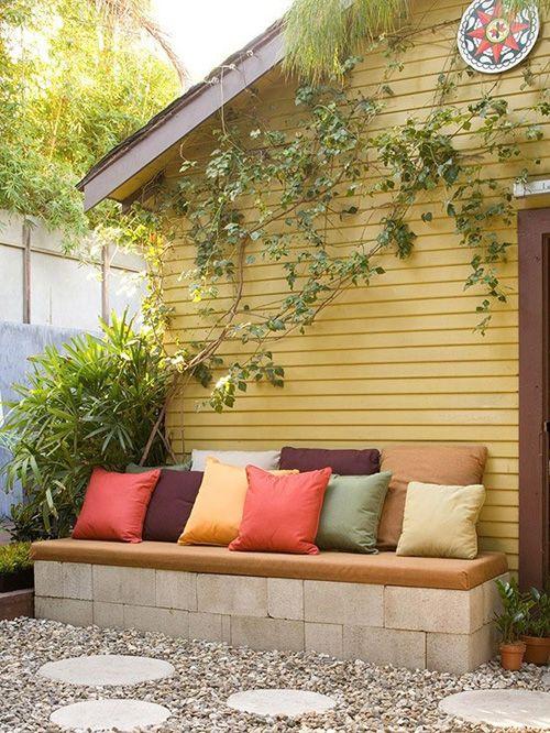 Banco de jardim de tijolo com almofadas coloridas
