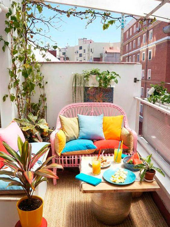 Banco de jardim rosa com almofadas coloridas