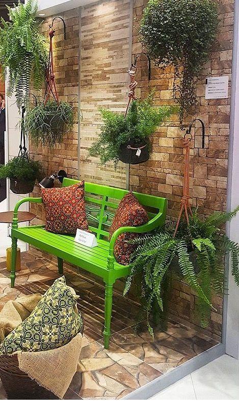 Banco de jardim verde com plantas suspensas
