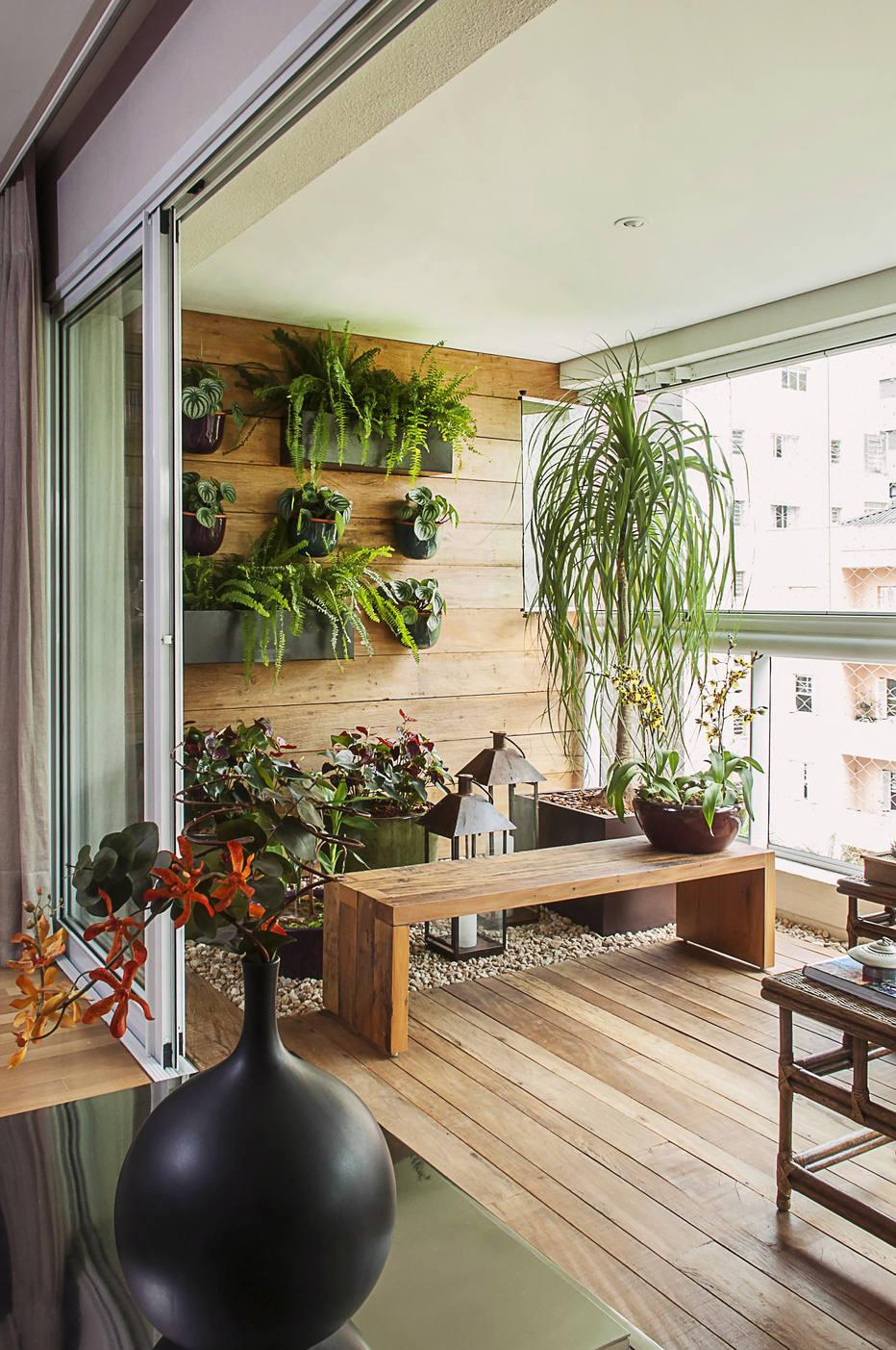 Varanda com jardim vertical e banco de madeira simples