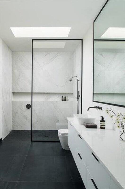 Banheiro com piso porcelanato preto e armário branco