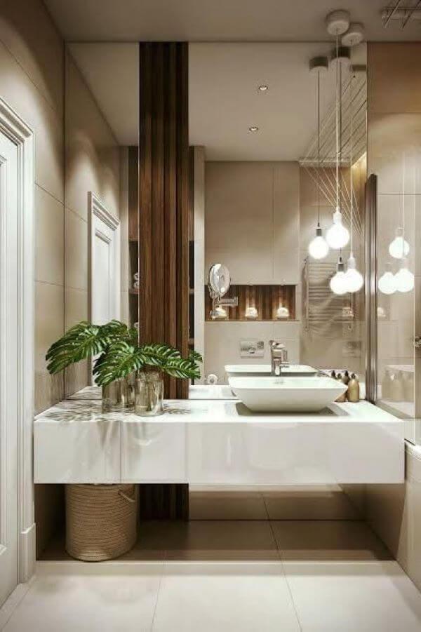 Banheiro com porcelanato branco e espelho na parede inteira