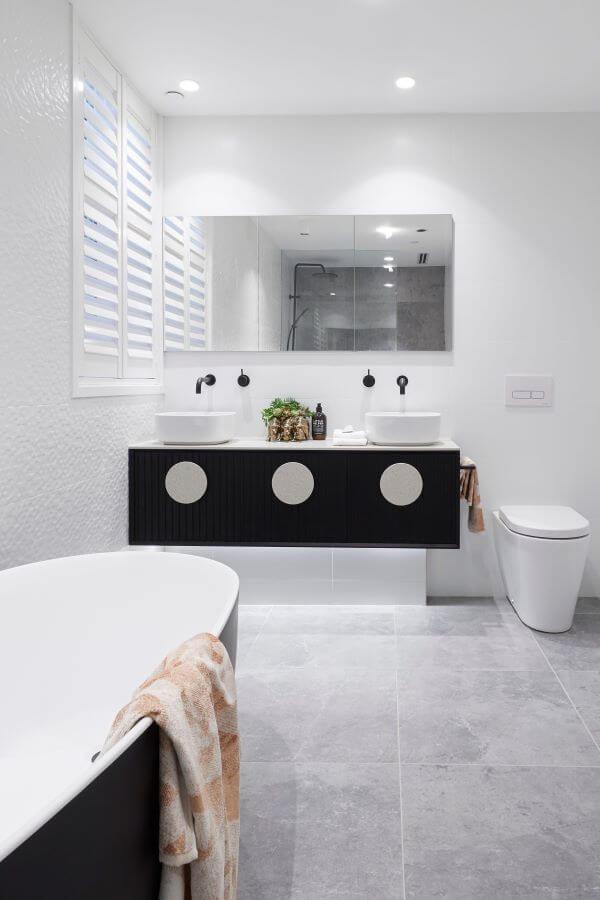 Banheiro com porcelanato cimento queimado com banheira preta