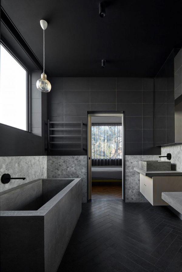 Banheiro com porcelanato preto e banheira cinza queimado