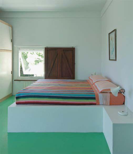 Cama de alvenaria e tijolo no quarto colorido