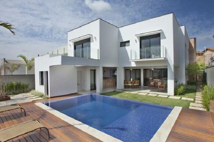 Casa moderna com piscina com prainha e deck de madeira. Projeto de Guardini Stancati
