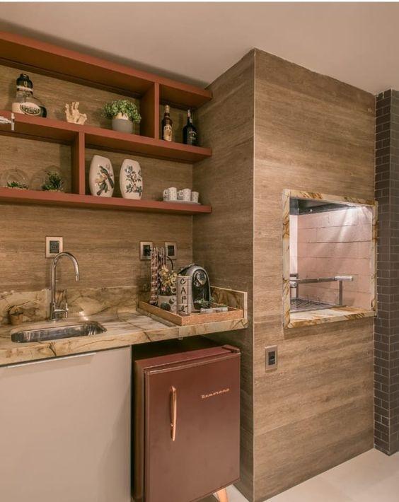 Churrasqueira de parede na cozinha planejada e revestimento de madeira